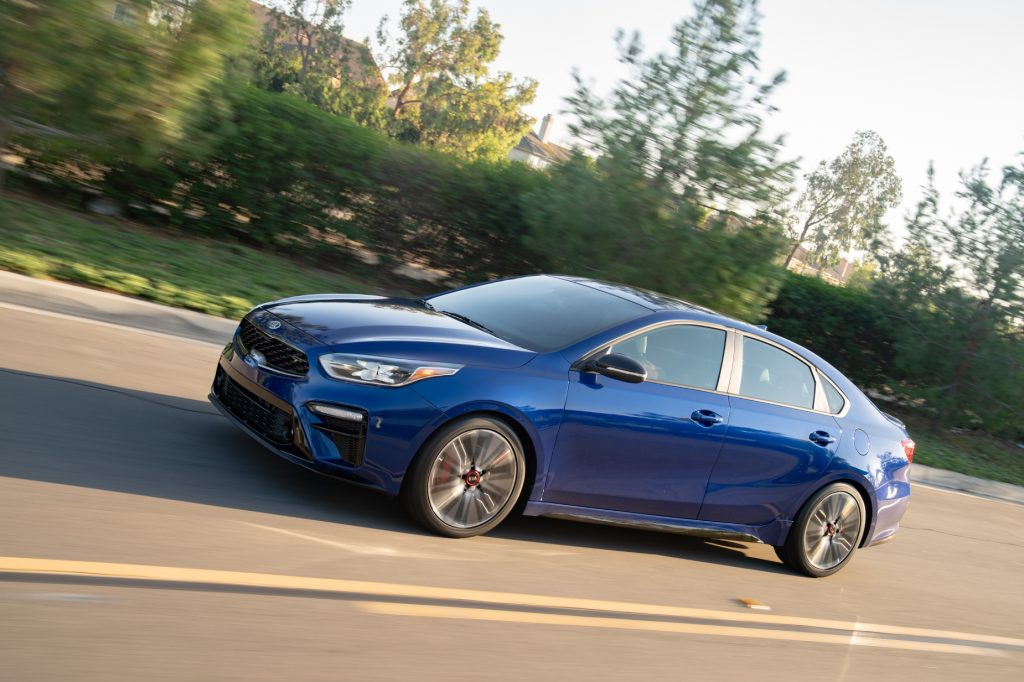 A blue 2021 Kia Forte displays its commuter car prowess while driving on the highway