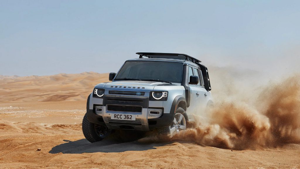 A silver 2021 Land Rover Defender 110 drives through the desert
