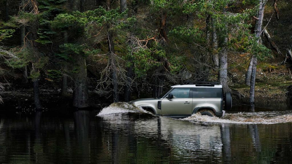A green 2021 Land Rover Defender 90 wades through a forest river