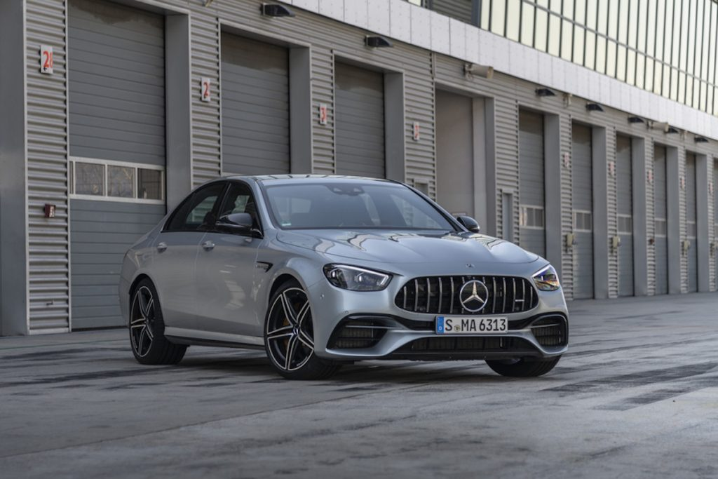 A press image of a silver 2021 Mercedes AMG E63 S sedan parked in front of an industrial building