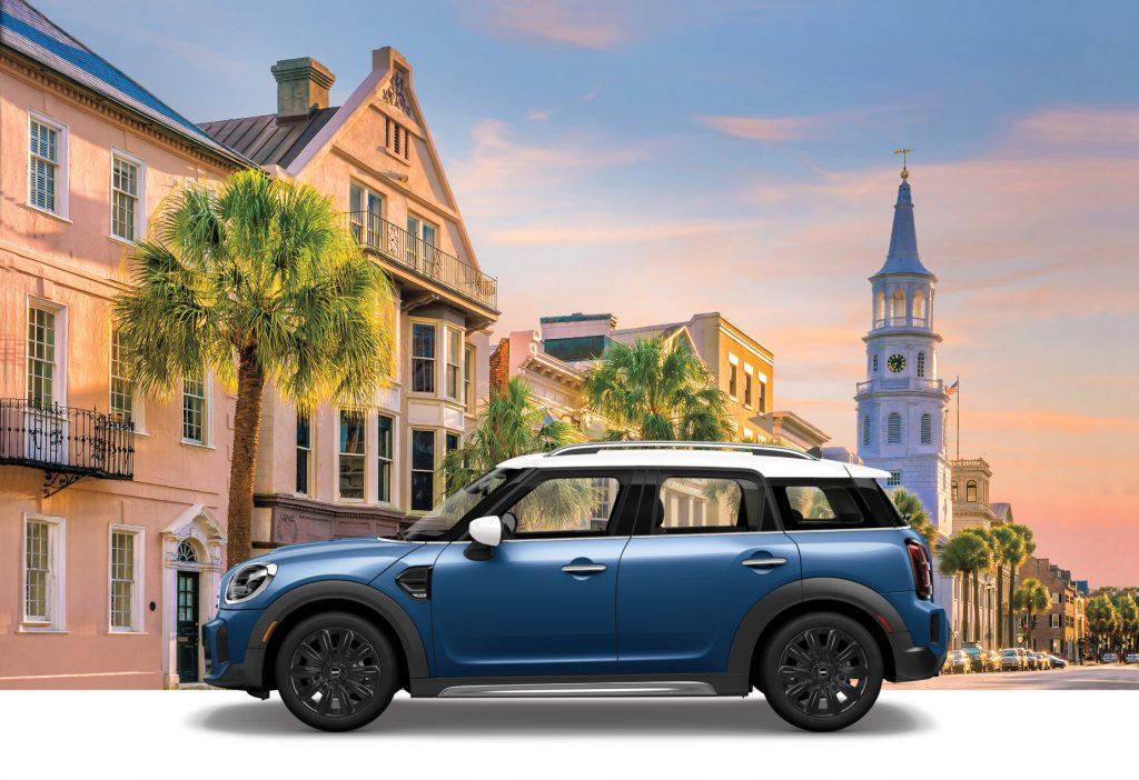 A blue 2021 Mini Countryman Oxford Edition on display with British scenery in the background.
