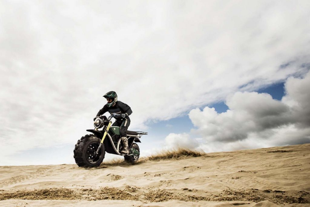 A rider tackles some dunes on a green 2021 Volcon Grunt