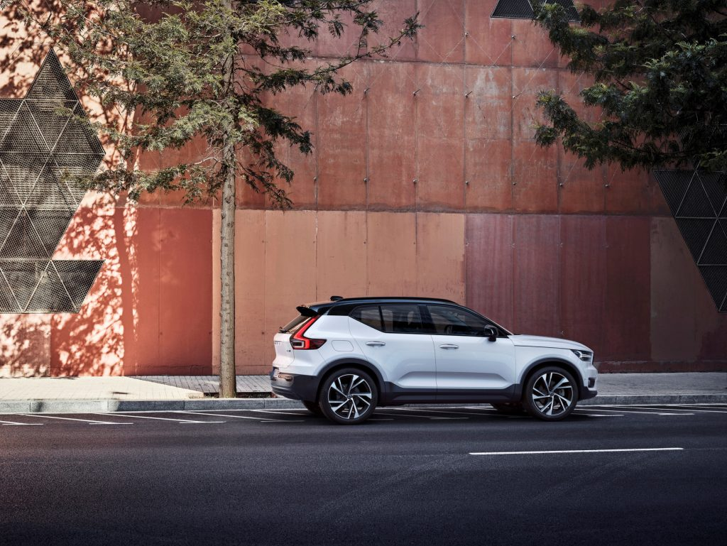 A white and black 2021 Volvo XC40 R-Design parked next to the side of a building