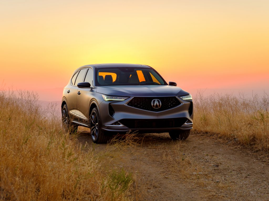 The 2022 Acura MDX prototype parked in a patch of grass with the setting sun in the background