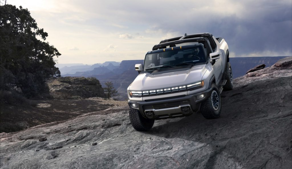 A silver 2022 GMC Hummer EV traversing rocky terrain