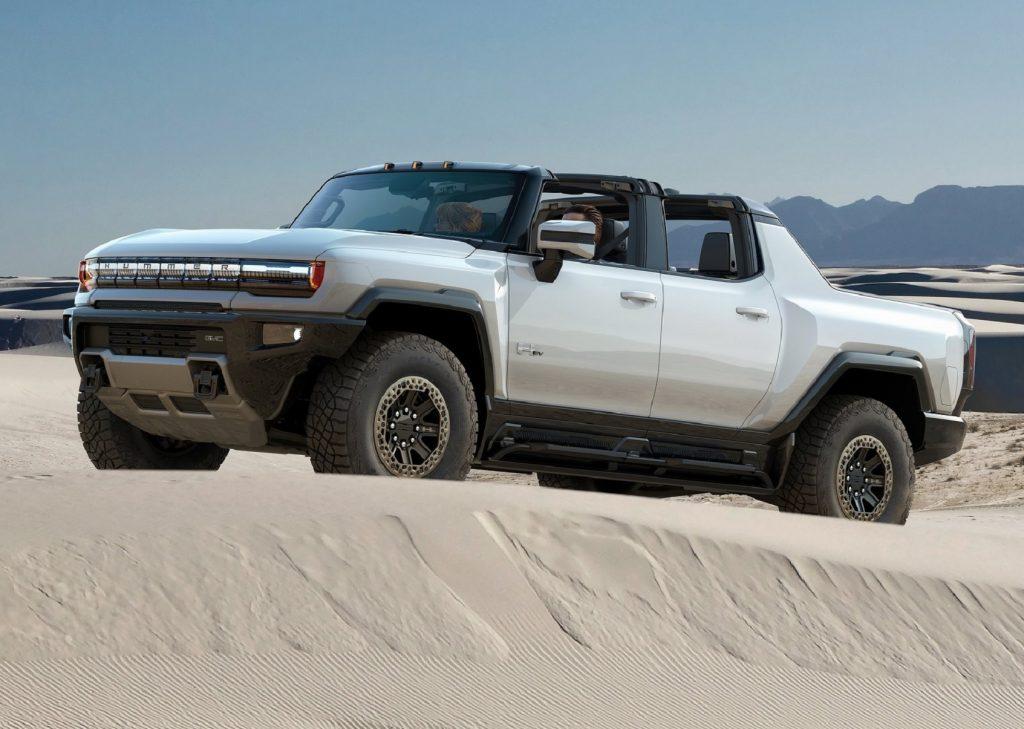 A white 2022 GMC Hummer EV climbs a dune