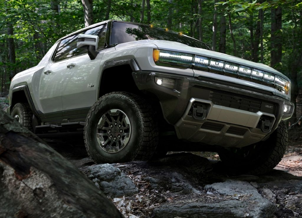 A white 2022 GMC Hummer EV scrambles over rocks in a forest