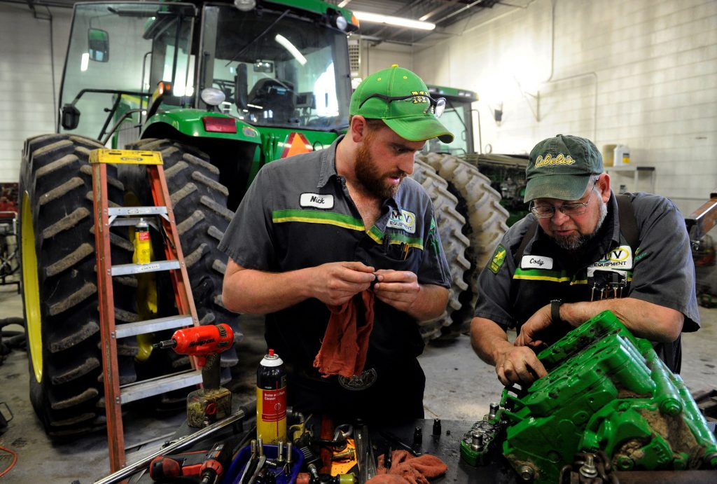 A master mechanic and service technician repair a John Deere tractor in a garage