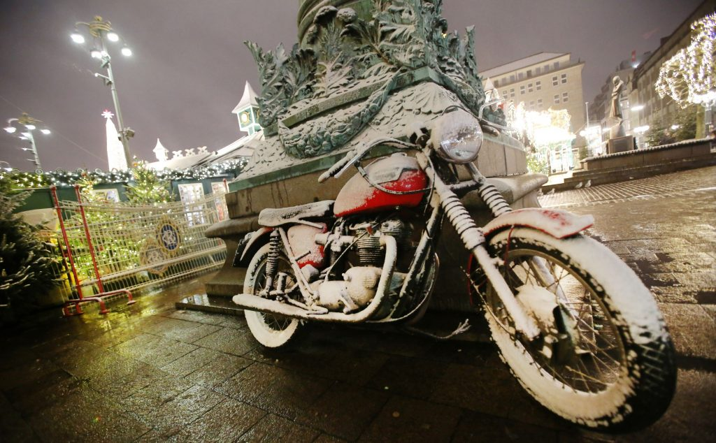 A red motorcycle covered in snow at a winter market