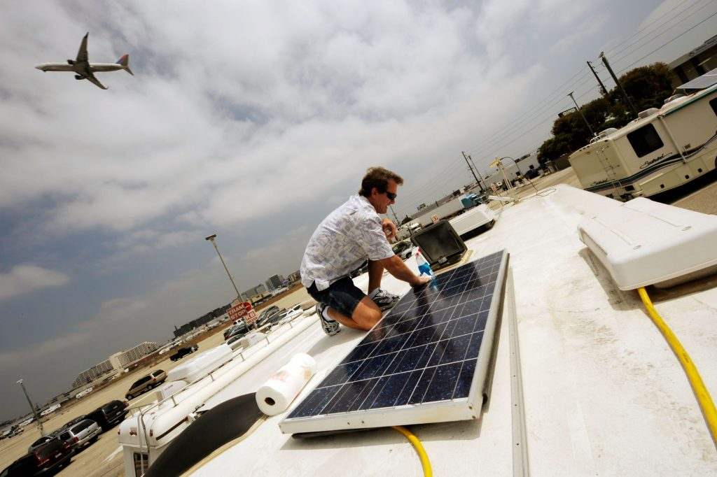 An aircraft mechanic does maintenance work on his RV's solar panels