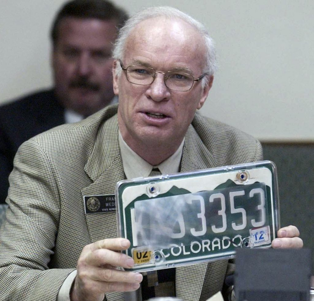 a man holding a covered-up license plate