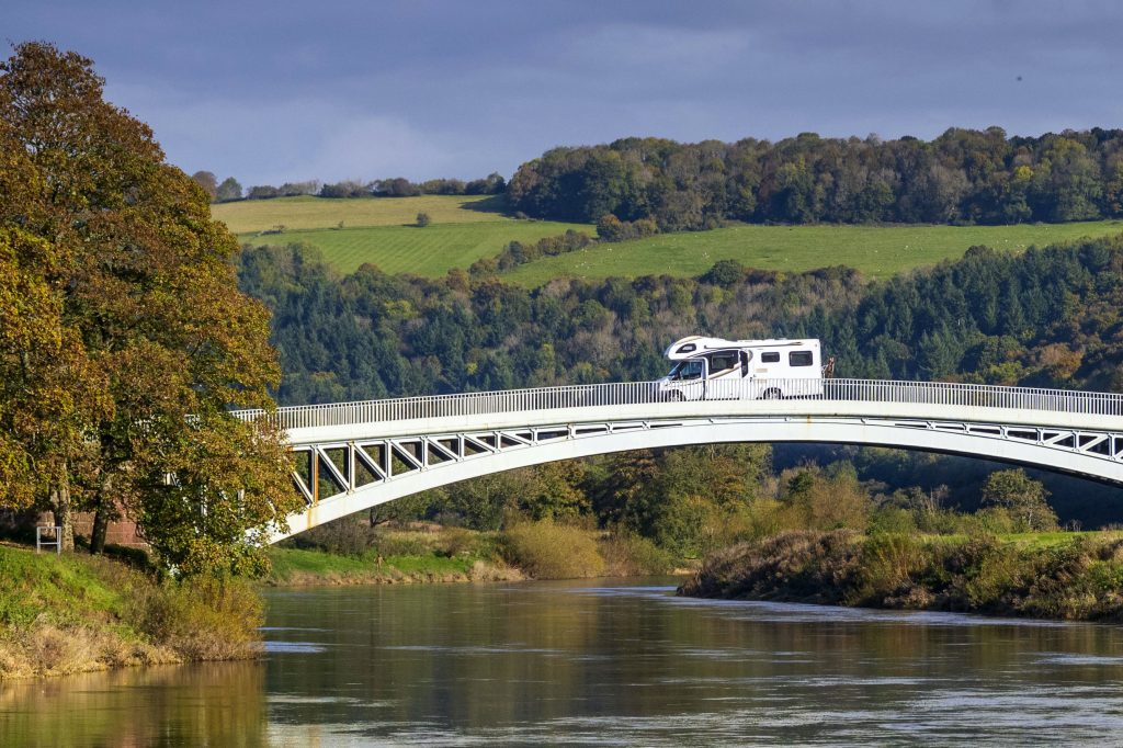 A camper van travels from the England to Wales over Bigsweir Bridge which spans the River Wye between Wales and England