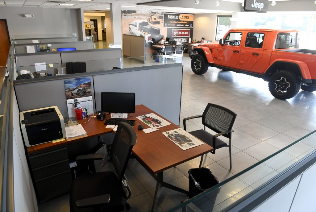 Car shopping: Empty desk at car dealership with Jeep in background