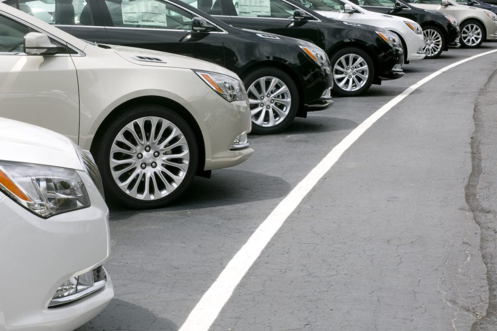 A row of sedans in a parking lot at a car dealership.
