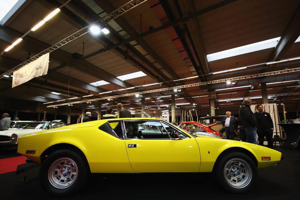 A yellow 1974 De Tomaso Pantera sits in an expo hall