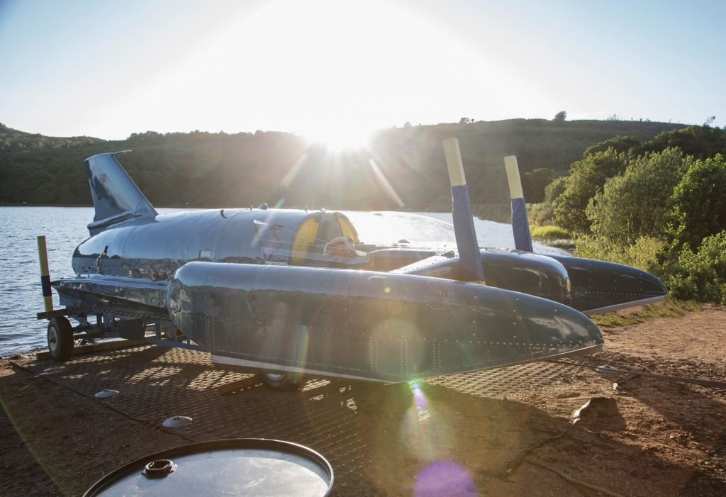 Donald Campbell's blue Bluebird hydroplane rests on its stand in front of a sunlit Scottish lake