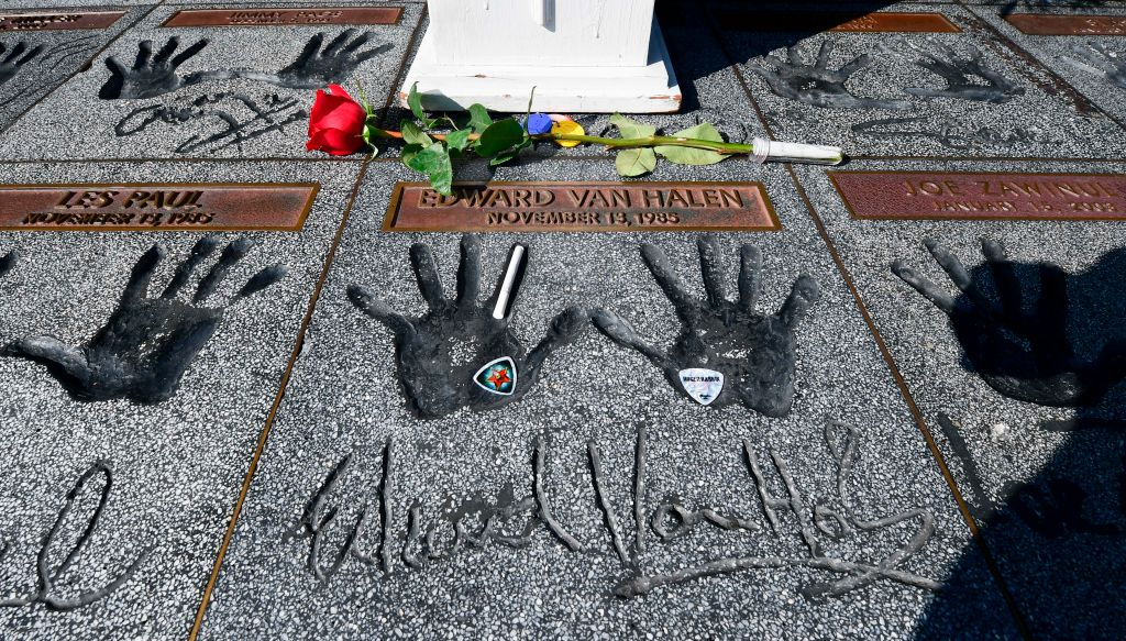 Momentoes including a rose, guitar picks and a cigarette are left on the handprints at the Guitar Center in Hollywood, California of rock guitarist Eddie Van Halen on October 6, 2020. - Van Halen placed his hands in the cement and was inducted into the Hollywood, California RockWalk on November 13, 1985. Eddie Van Halen, the guitar virtuoso whose group is considered one of the greatest rock bands of all time, died on October 6, 2020 following a long battle with cancer, his son announced. (Photo by Frederic J. BROWN / AFP) (Photo by FREDERIC J. BROWN/AFP via Getty Images)