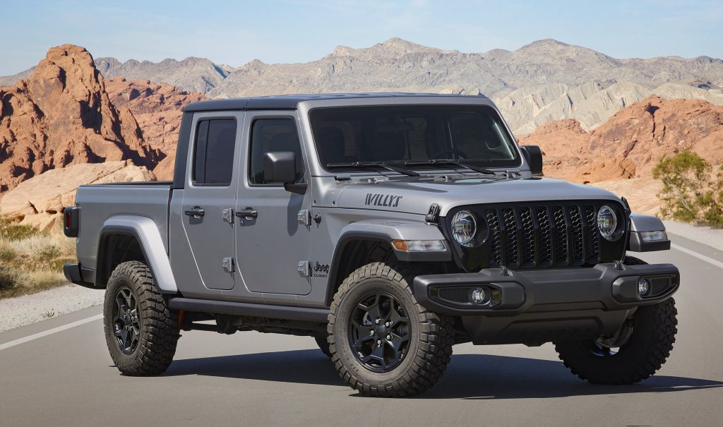 A Sting Gray 2021 Jeep Gladiator Willys in the middle of a road with a mountain backdrop