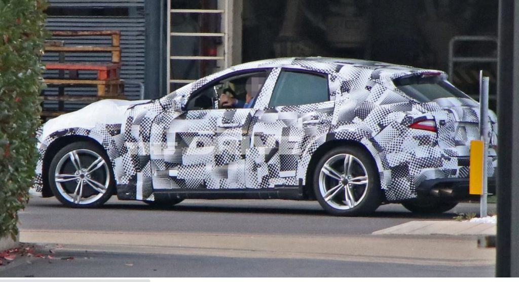 A Ferrari test mule for the Purosangue SUV is wrapped in spy camouflage.