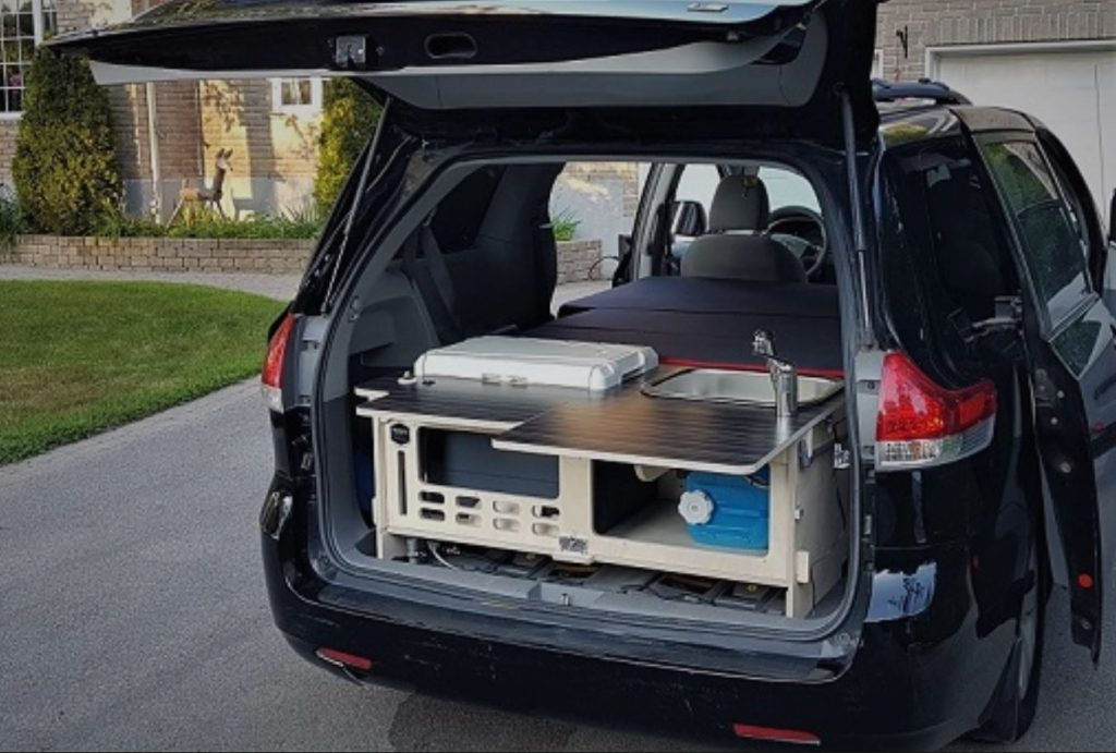 The back of a Toyota Sienna minivan has the Malibu 2 kit installed make a functional RV camper.