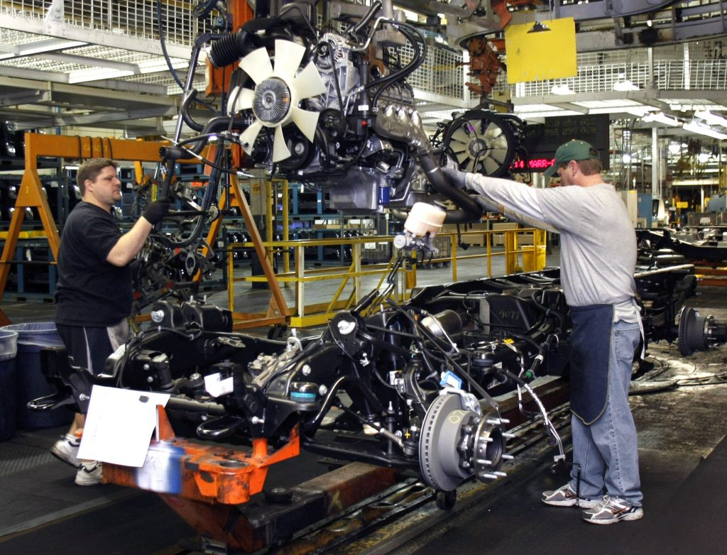 Workers assemble an engine at a GMC factory