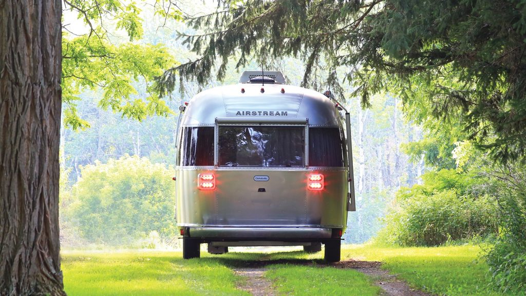 A gray Airstream Globetrotter camper off-road in the woods.