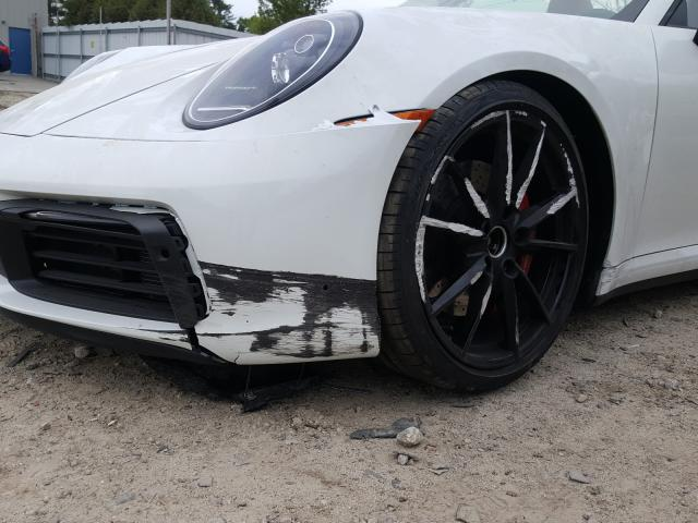 some damage on the front bumper and wheel of a white Porsche