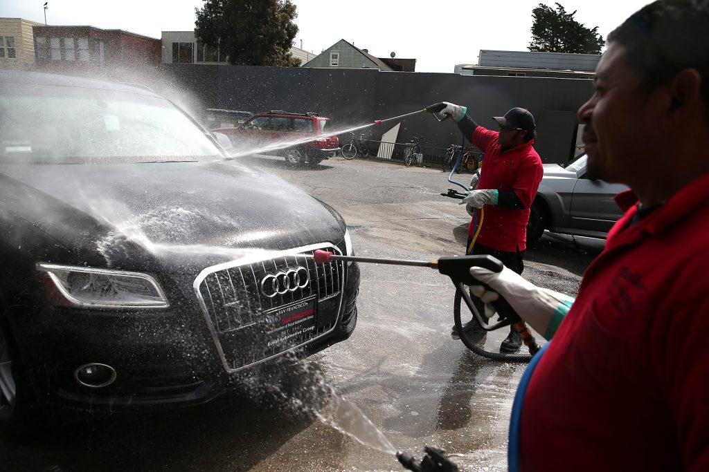 Two workers aim pressure washers at an Audi to clean off the paint finish