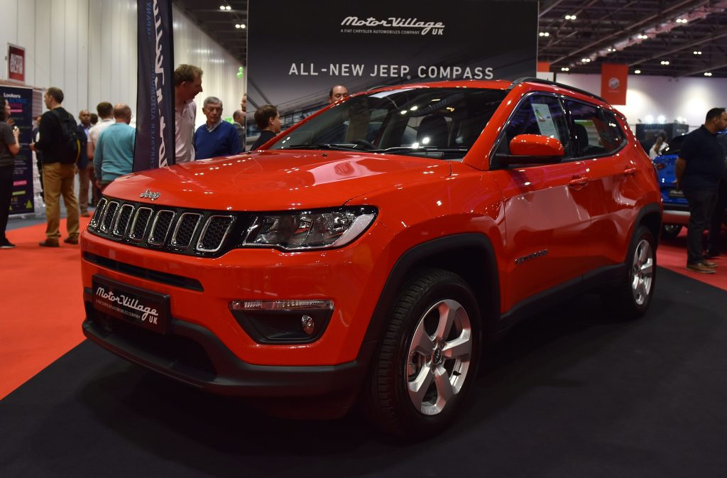 A red Jeep Compass on display at an auto show