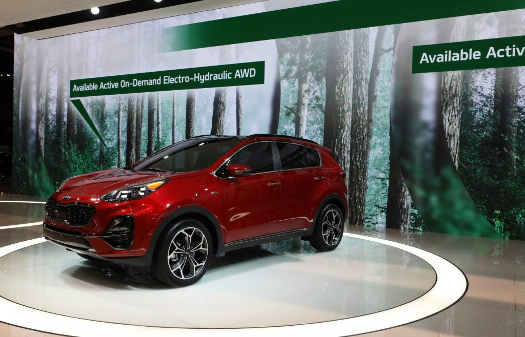 A Kia Sportage on display at an auto show advertising its available all-wheel-drive system
