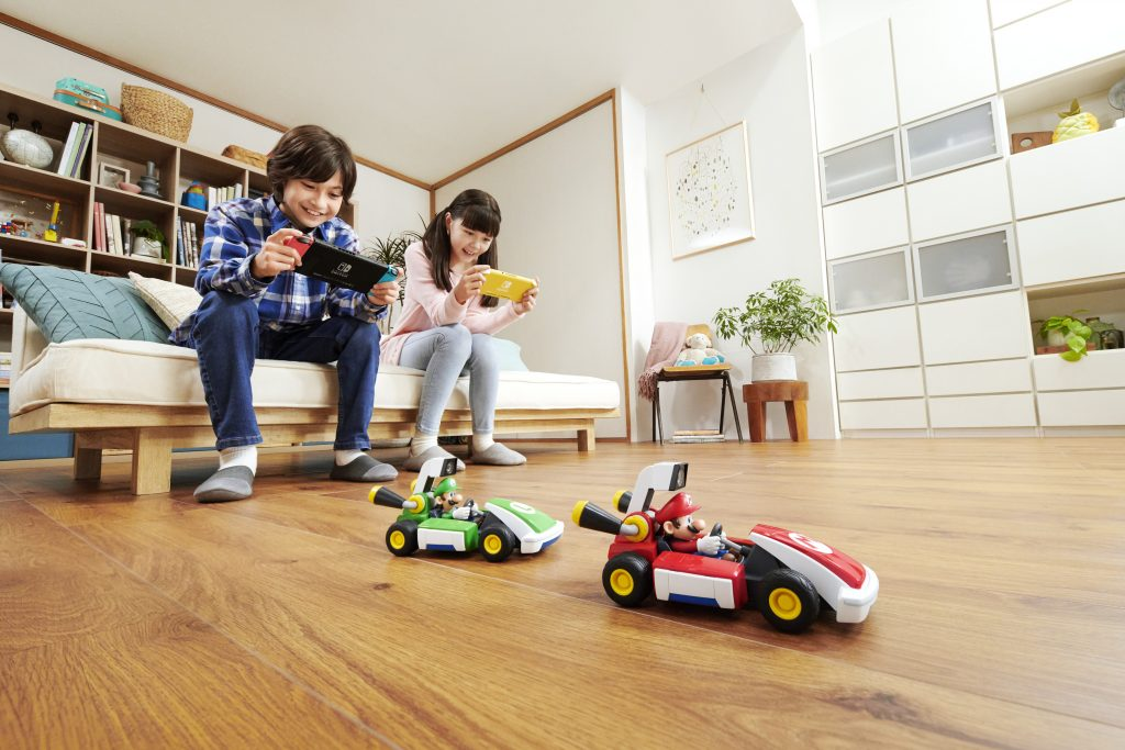 Two children holding Nintendo Switches as they control their vehicles for Mario Kart Live Home Circuit
