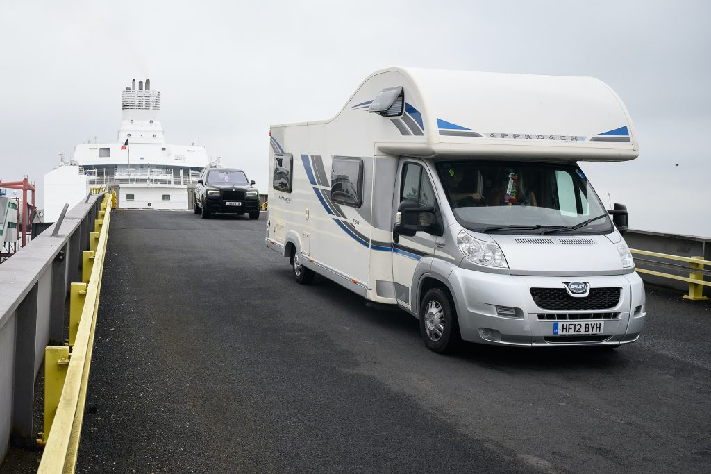 A motorhome RV drives down the exit ramp as travelers from France disembark from a Brittany Ferries ship