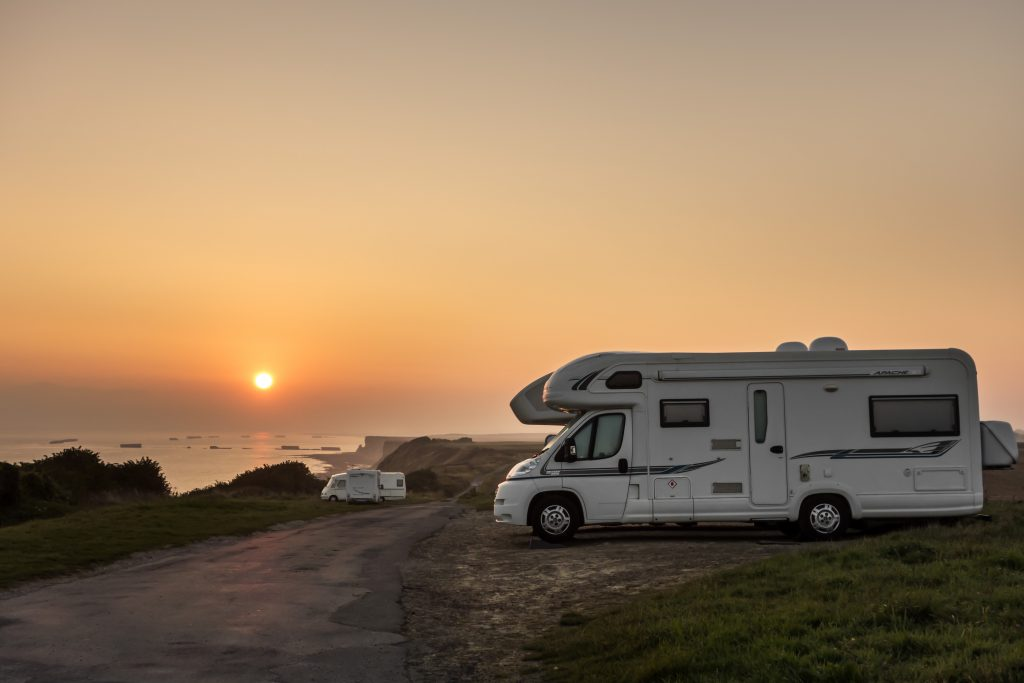 Motorhomes parked along the coast at sunset with view over the sea