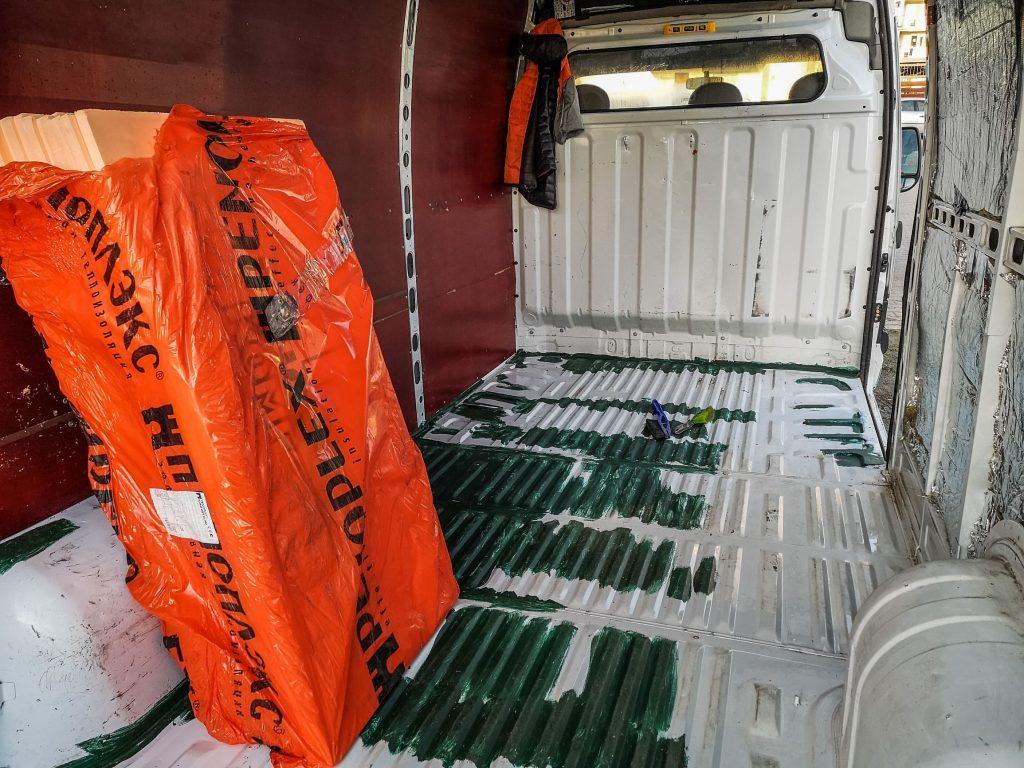 Orange Penoplex polystyrene insulation boards in a stripped-down camper van