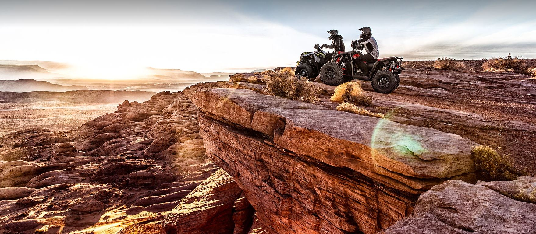 two Polaris Scrambler XP 10000 S ATV riders parked at the edge of a cliff watching the sunrise