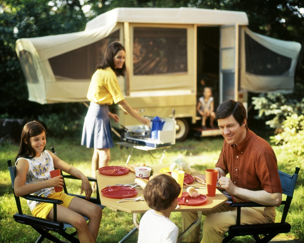 A family smiles outside of their pop-up camper