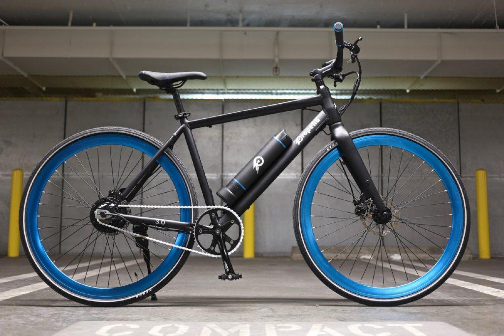 A black-framed blue-wheeled Propella 7-Speed Version 4.0 e-bike in a parking garage