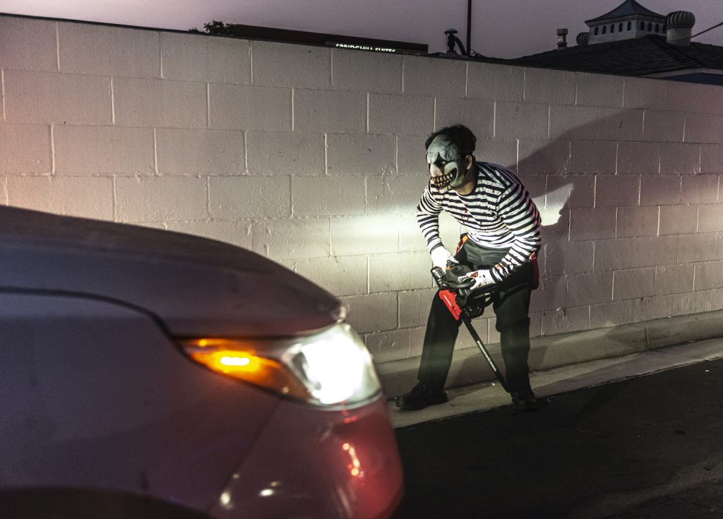 A person in Halloween costume in front of a car