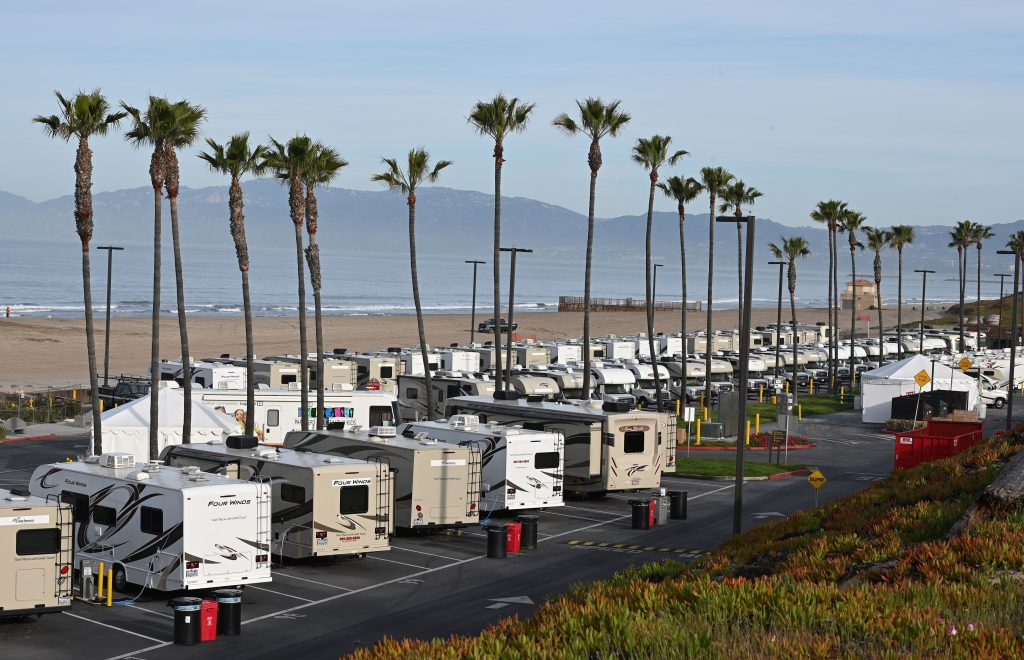 RVs parked at a lot by the ocean