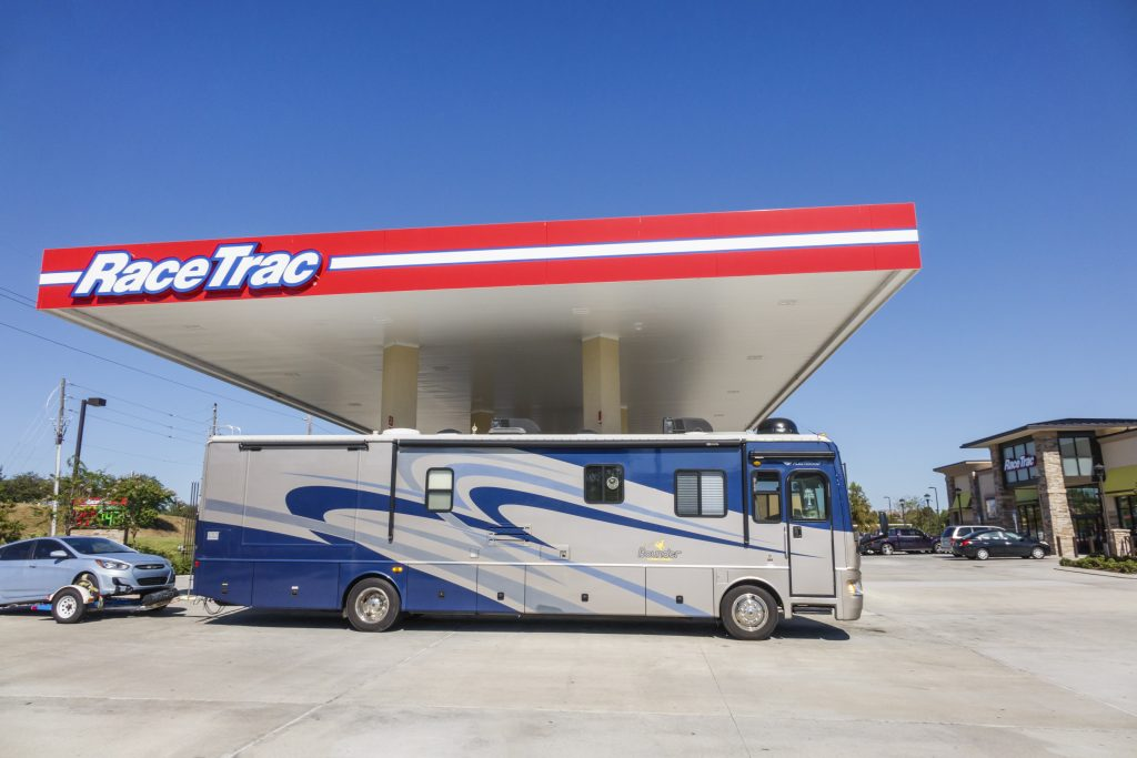 A full-size RV towing a car refuels under a gas station roof