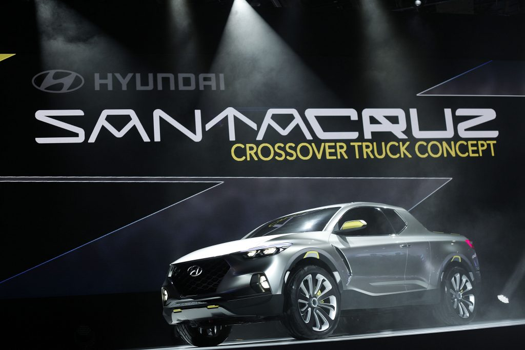 A silver extended cab pickup sits on stage. It is the Santa Cruz concept from Hyundai.