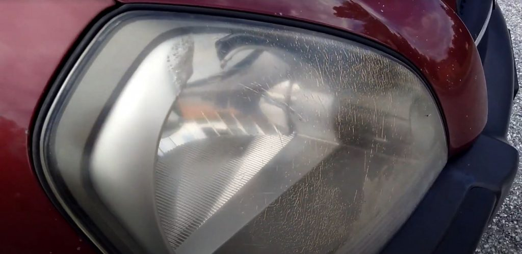 A headlight with stress cracks and fading.
