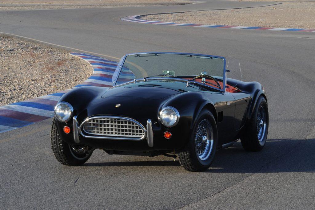 A black Shelby Street Cobra 289 on a racetrack