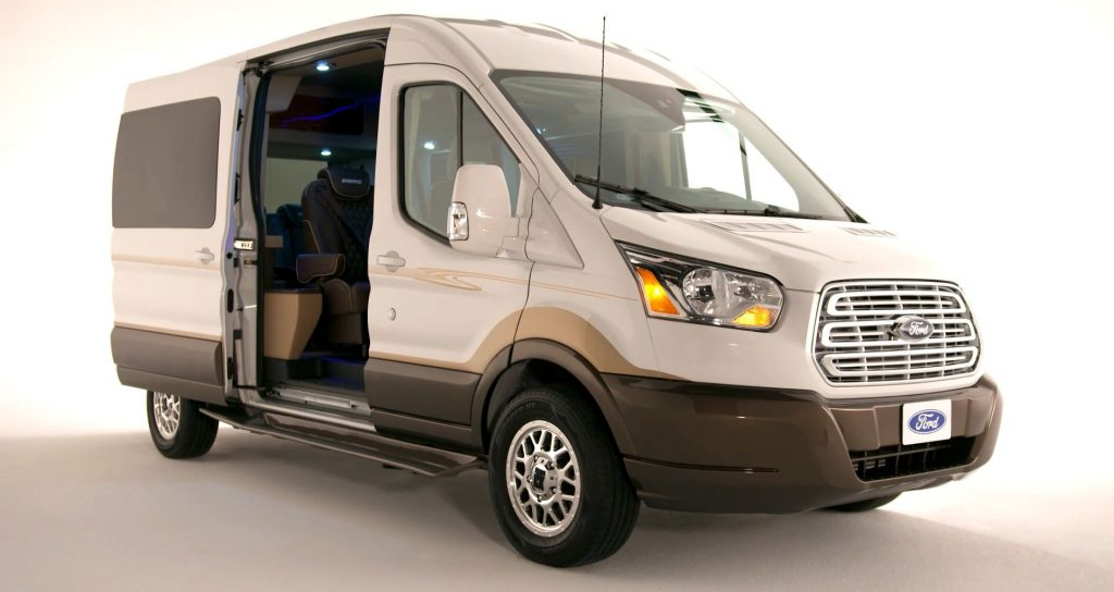 A white, full-size, conversion van based on a Ford Transit.