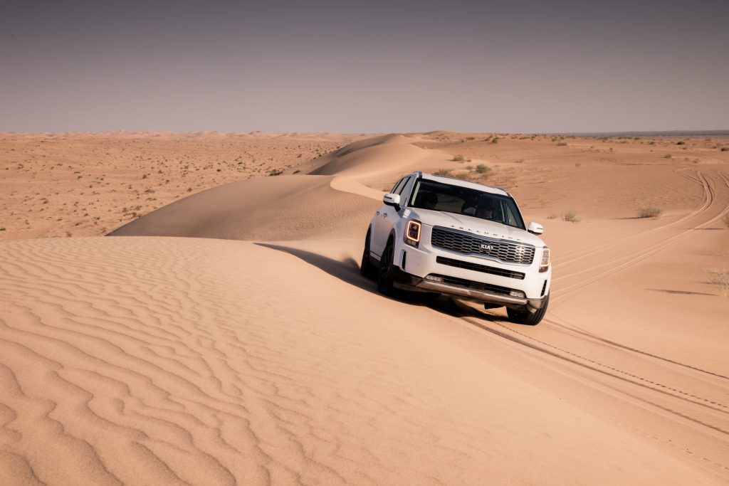 A white Kia Telluride is traveling on sand dunes.
