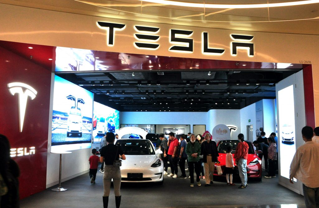 People look at electric vehicles at a Tesla store