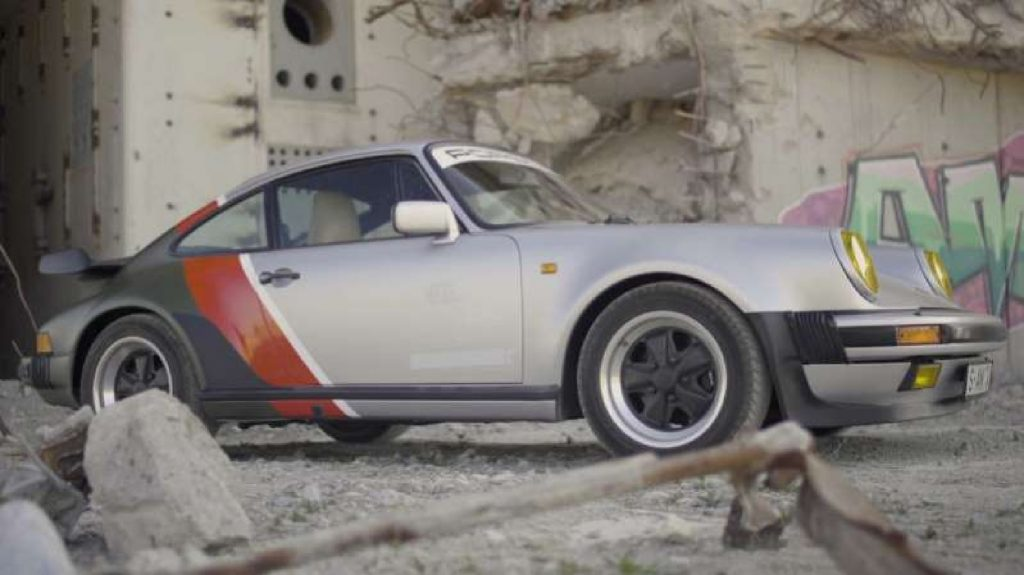 The silver-red-green Cyberpunk 2077-inspired 1977 Porsche 930 911 Turbo next to a graffitied concrete wall