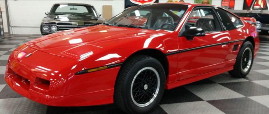 A red Pontiac Fiero sits on a showfloor.
