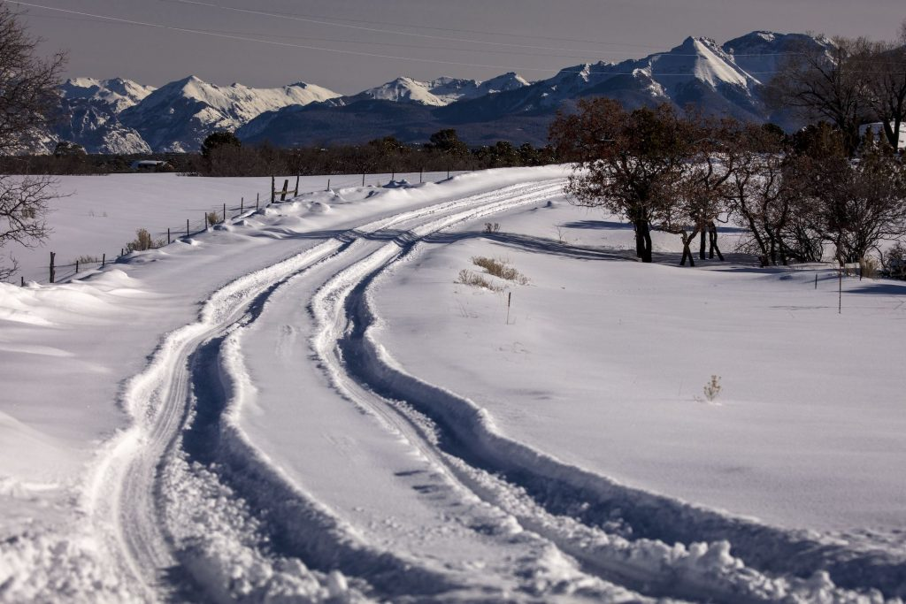 Winter snowy road through deep snow leads to San Juan Mountains. Overlanding at its best.