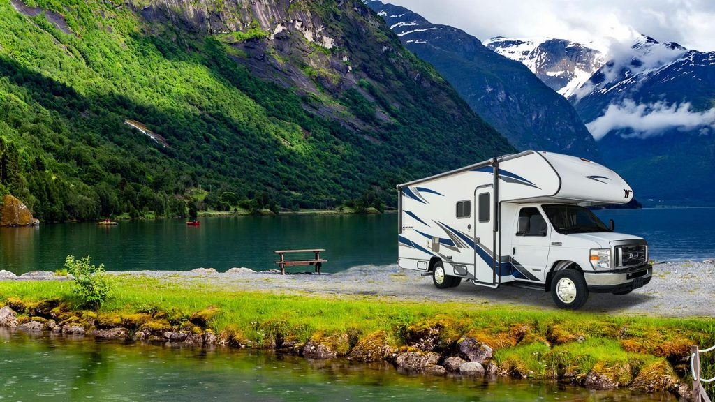 A white Winnebago Outlook with dark accents. on the countryside.